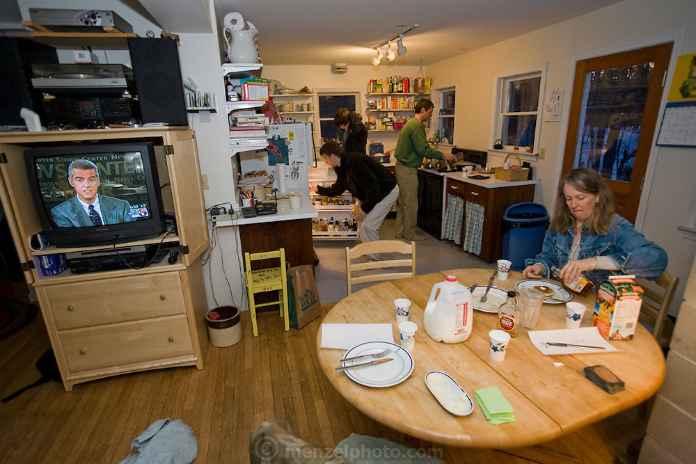 Lobsterman and fish buyer Sam Tucker (center at sink) makes pancakes at his home on Great Diamond Island, Maine, while his wife and sons prepare to have breakfast. (Samuel Tucker is featured in the book What I Eat: Around the World in 80 Diets.) MODEL RELEASED.