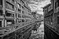 Black and white view of the French Alps, and colorful buildings along the reflective waters of Thiou Canal, Old Town Annecy, France.