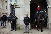A tourist poses for a photograph in front of a mounted soldier from the Household Cavalry and a heavily armed metropolitan police officer at  at Horseguards in Whitehall, London, UK. Friday January 5th 2018