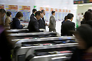 commuters rushing through the turnstile Japan Tokyo
