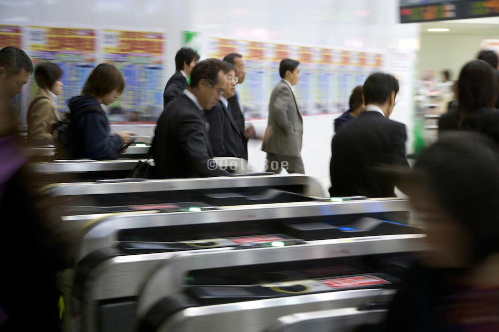 commuters rushing through the turnstile Japan Tokyo