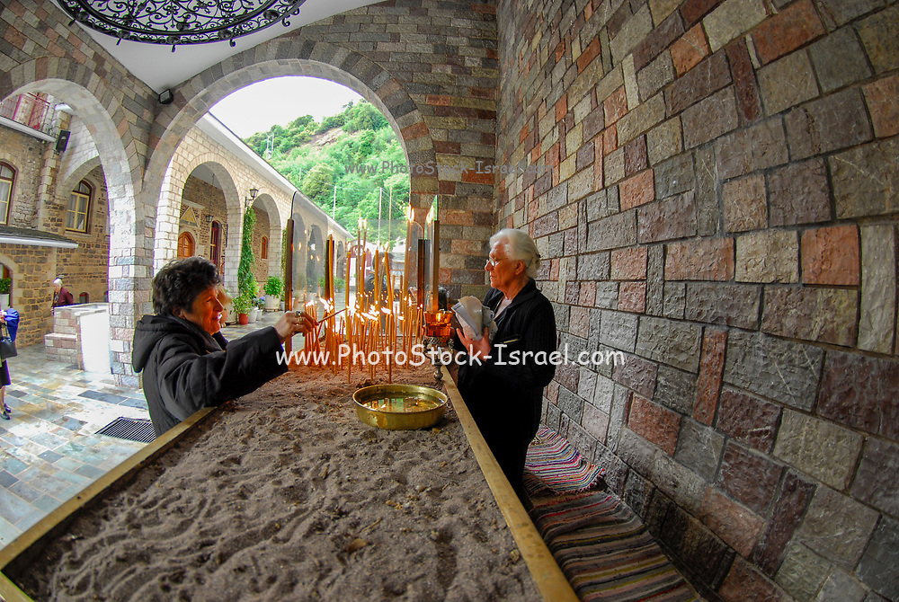 Lighting candles in a monastery in Greece