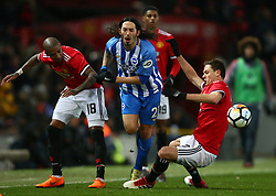 Manchester United's Ashley Young, left, and Manchester United's Nemanja Matic, right, tackle Brighton & Hove Albion's Ezequiel Schelotto