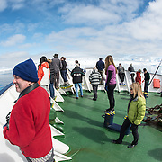 Passenger stand up on deck watching for whales in Fournier Bay in Antarctica.