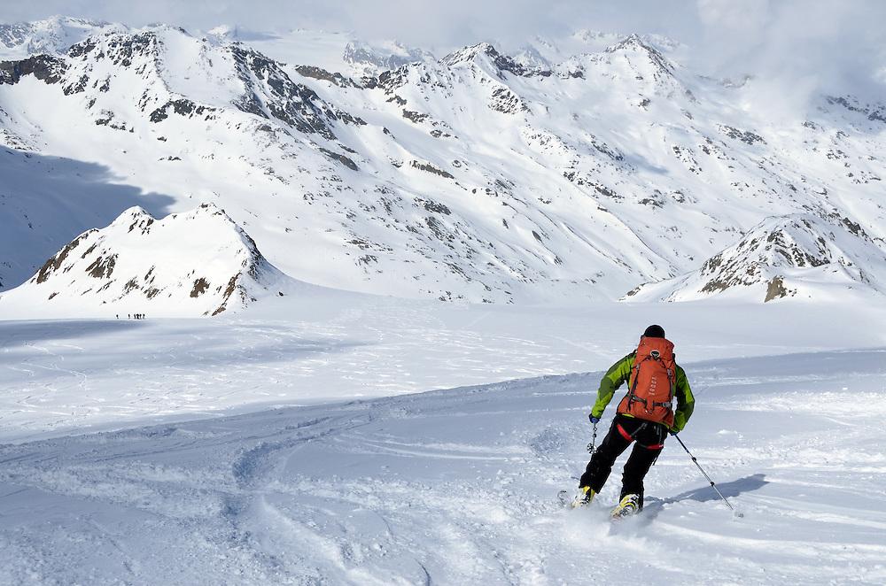 Backcountry skier telemarking in Otztal Alps on the Austria/Italy border.