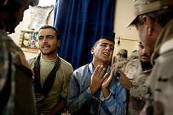 Captured insurgents Imad Shaeb, also known as Adel, and Ahmed Mohammed Ali, also known as Neshuan, plead with members of the Iraqi Army Battalion 222, Mosul, Iraq, Dec. 11, 2005. The men were taken out of Iraqi Police custody by American forces. Members of the 1st Infantry, 17th Regiment, help Iraqi forces patrol as part of an effort to provide security in preparation for Iraq's first post-Saddam parliamentary elections. The western sector is home to Mosul's primarily Sunni population, which has been resistant to the American presence in Iraq.