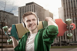 Teenage boy with skateboard on shoulders and listen to music in the street, Bavaria, Germany