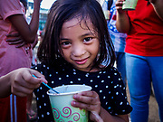 """26 JANUARY 2017 - MALILIPOT, ALBAY, PHILIPPINES: A girl who lives on the slopes of the Mayon volcano eats a """"champorado,"""" a Filipino sweet of sticky rice, coconut milk and chocolate, provided by the Philippine Red Cross in the shelter in Malilipot. The volcano was relatively quiet Friday, but the number of evacuees swelled to nearly 80,000 as people left the side of  the volcano in search of safety. There are nearly 12,000 evacuees in Santo Domingo, one of the communities most impacted by the volcano. The number of evacuees is impacting the availability of shelter space. The Philippines is now preparing to house the volcano evacuees for up to three months.    PHOTO BY JACK KURTZ"""