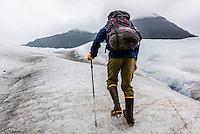 A mountain guide walking on the Mendenhall Glacier, Juneau, Alaska USA.