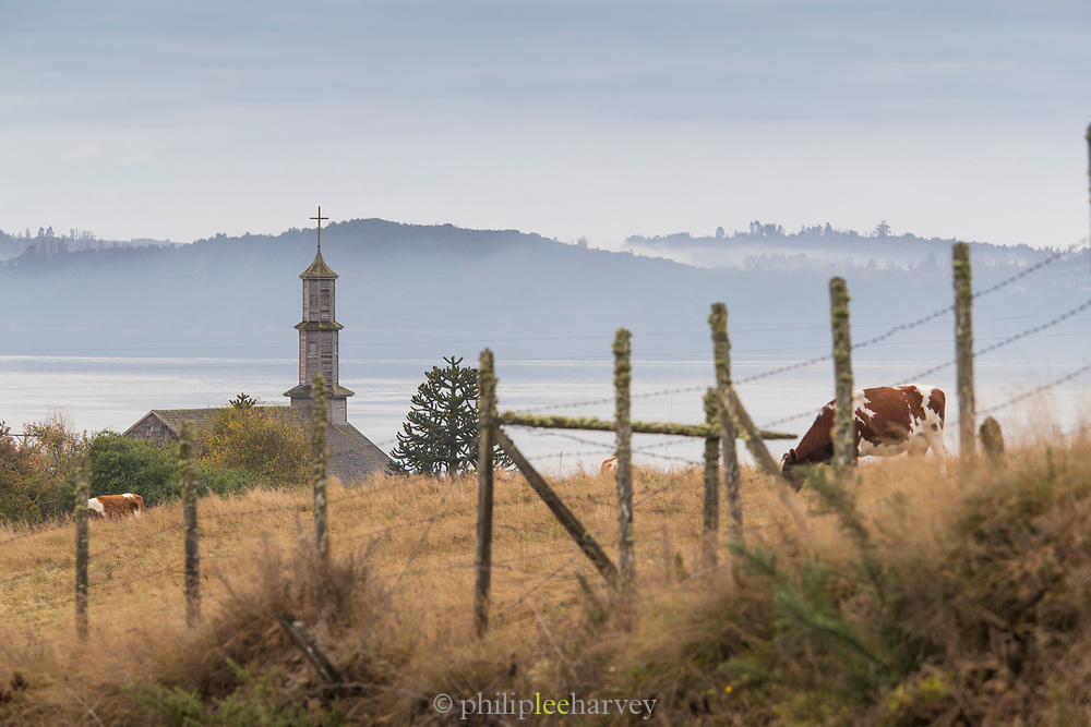 View of mountains, sea and exterior of Church of Vilupulli, Chiloe Island, Chile
