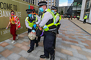 An arrestee who is being carried the Police wearing face masks (R), meanwhile a legal observer (L) wearing an orange jacket and face mask is observing the process. The arrestee is suspected to have sprayed 'STOP ECOCIDE' outside Shell Headquarters building in Jubilee Gardens, Central London, on Tuesday, Sept 8, 2020. Protestors are seeking to step up pressure on Shell and demand an end on fossil fuel extraction as well as ecocide. Environmental nonviolent activists group Extinction Rebellion enters its 8th day of continuous ten days protests to disrupt political institutions throughout peaceful actions swarming central London into a standoff, demanding that central government obeys and delivers Climate Emergency bill. (VXP Photo/ Vudi Xhymshiti)