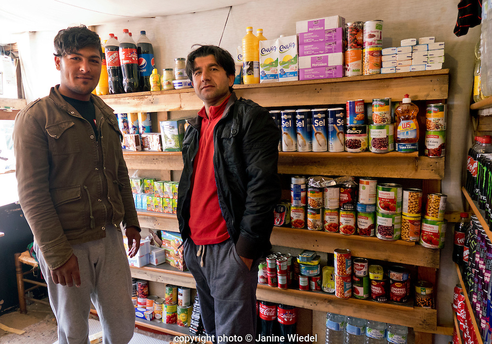 Shopkeepers inside shop selling provisions in the Calais Jungle Refugee and Migrant Camp in France
