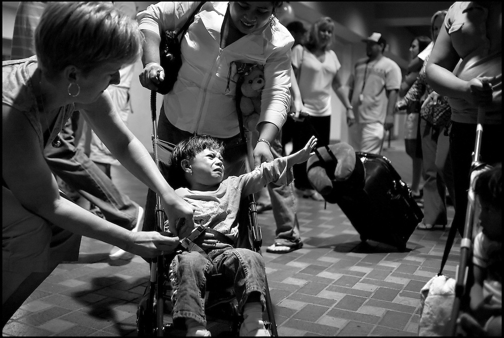 Arriving in Albuquerque after their first trip on an airplane, 2-year-old Marta Melera cries out for her mother, Juana (behind), as host mother Libby Bombach tries to get her settled into her stroller. They came to Albuquerque so Marta could have heart surgery through a program called Healing the Children.
