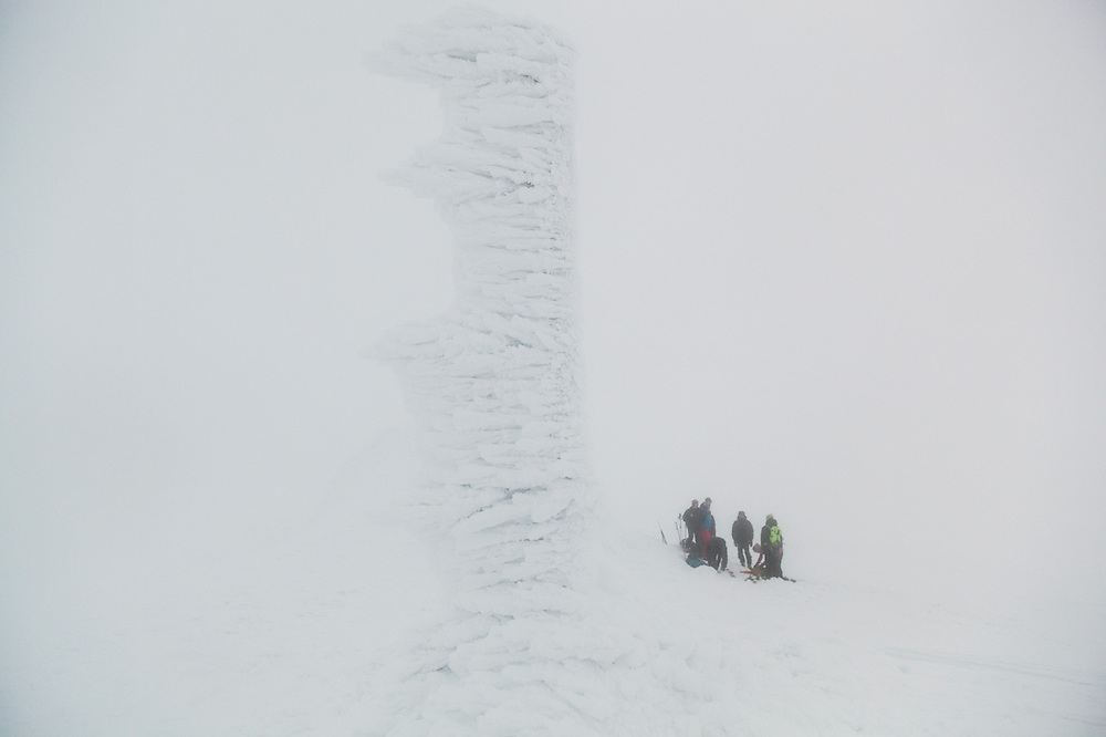 Backcountry skiers gather on the windy, frost covered summit of Nordenskiöldfjellet, Svalbard.