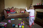 Children playing in the living room of their family home. Leyland, Lancashire.