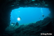 divers swim into cavern at Niihau Arches dive site between Lehua Rock and Niihau Island, Hawaii, USA ( Central Pacific Ocean )