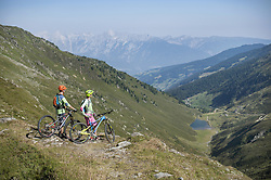 Young couple of mountain bikers looking at view in alpine landscape, Zillertal, Tyrol, Austria