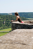Female leaning against castle wall looking over countryside, Germany