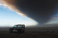 Ashfall from Volcano Eyjafjallajökull on Dyrhólaey beach, South Iceland. Land Rover beneath ashcloud,