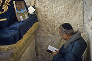 A jewish man prays in front of the sarcophagus believed to be King David's burial place. The tomb is located in a corner of a room situated on the ground floor remains of the former Hagia Zion an ancient house of worship; the upper floor of the same building has traditionally been viewed as the Cenacle of Jesus. The site was apparently not viewed as David's Tomb until the 12th century. According to Benjamin of Tudela, writing about 1173, the tomb was discovered during repairs to the church; the motivation for it being declared to be the tomb of David is due to Davids conquest of Mount Zion described in the Book of Samuel. The contents of the sarcophagus have not yet been subjected to any scientific analysis, to determine their age, former appearance, or even whether there is actually still a corpse there.