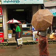 Men wearing longyi at the streets of downtown Yangon during rainfall