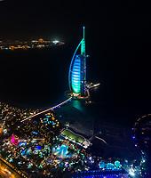 Aerial view of the luxurious Burj Al Arab Hotel by night in Dubai bay, U.A.E.