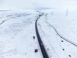Dalwhinnie, Scotland, UK. 6 May 2021. Aerial view of snow covered landscape in the high altitude Drumochter Pass at Dalwhinnie in the Scottish highlands. Pic; The A9 highway winds its way north through a snow covered Drumochter Pass. Iain Masterton/Alamy Live News