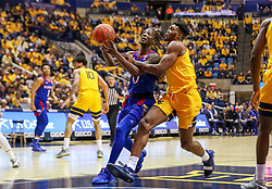 Feb 12, 2020; Morgantown, West Virginia, USA; Kansas Jayhawks guard Marcus Garrett (0) drives down the lane while defended by West Virginia Mountaineers forward Derek Culver (1) during the first half at WVU Coliseum. Mandatory Credit: Ben Queen-USA TODAY Sports