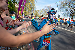 © Licensed to London News Pictures. 22/04/2018. London, UK. A fancy dress marathon runner high fives members of the public on Embankment during the Virgin Money London Marathon 2018. Photo credit: Rob Pinney/LNP