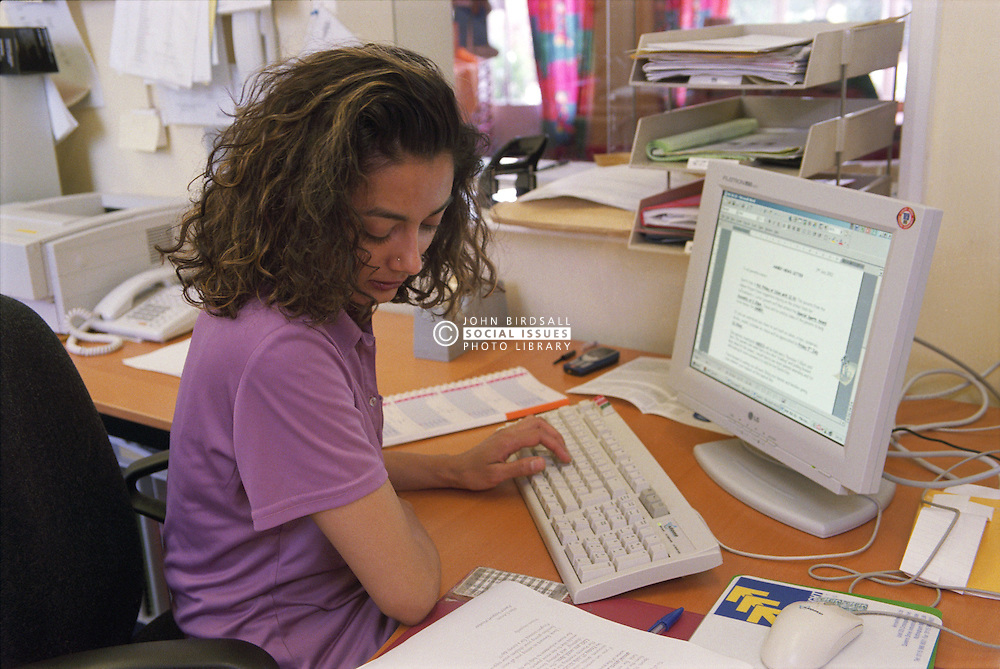 Young woman sitting at desk in school office using computer,