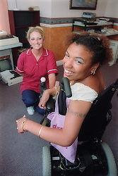 Young woman with cerebral palsy using wheelchair; smiling with carer,