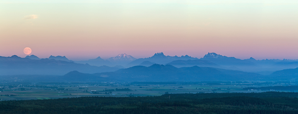The moon rises over mountain peaks in the North Cascades just after sunset. Photographed from the top of Mt. Erie in Anacortes, Washington State, USA. The main peaks here (from L to R) are Round Mountain, Mount Higgins, Glacier Peak, White Chuck Mountain, Whitehorse Mountain Three Fingers, and Liberty Mountain.