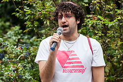 London, UK. 6 July, 2019. Adam Eli of Voices4 addresses activists from Lesbians and Gays Support The Migrants, African Rainbow Family, the Outside Project, Micro Rainbow and other LGBT+ groups preparing to take part in a London Pride Solidarity March in solidarity with those for whom Pride in London is inaccessible and in protest against the corporatisation of Pride in London.