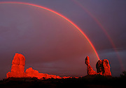 A passing storm brings a double rainbow in Arches National Park as the rock formation known as Balanced Rock glows from the setting sun. Colin Eric Braley