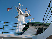 a flag, radar and communications antennae on a Washington State Ferry against a blue sky in Puget Sound, Washington, USA
