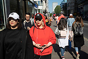 Red, hoodie, NY hats and headphones along Oxford Street in London, England, United Kingdom. This is the busiest shopping district in the capital with Oxford Street being the most crowded. Crowds can be so big that many people avoid the area altogether.