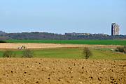 Nederland, Heerlen, 26-3-2018Stadsgezicht Heerlen vanuit de landelijke omgeving gezien. Een boer op een tractor rijdt op zijn akker.Foto: Flip Franssen