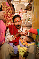 A father acepts a donation while holding his ill child during the festival of Kartik Poornima in Varanasi, Uttar Pradesh, India
