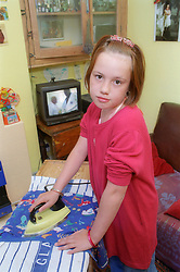 Young girl ironing clothes in front of the television,