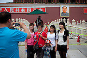 "A family is getting photographed at the main gate of ""The Forbidden City"" which was the Chinese imperial palace from the Ming Dynasty to the end of the Qing Dynasty. It is located in the middle of Beijing, China. Beijing is the capital of the People's Republic of China and one of the most populous cities in the world with a population of 19,612,368 as of 2010."
