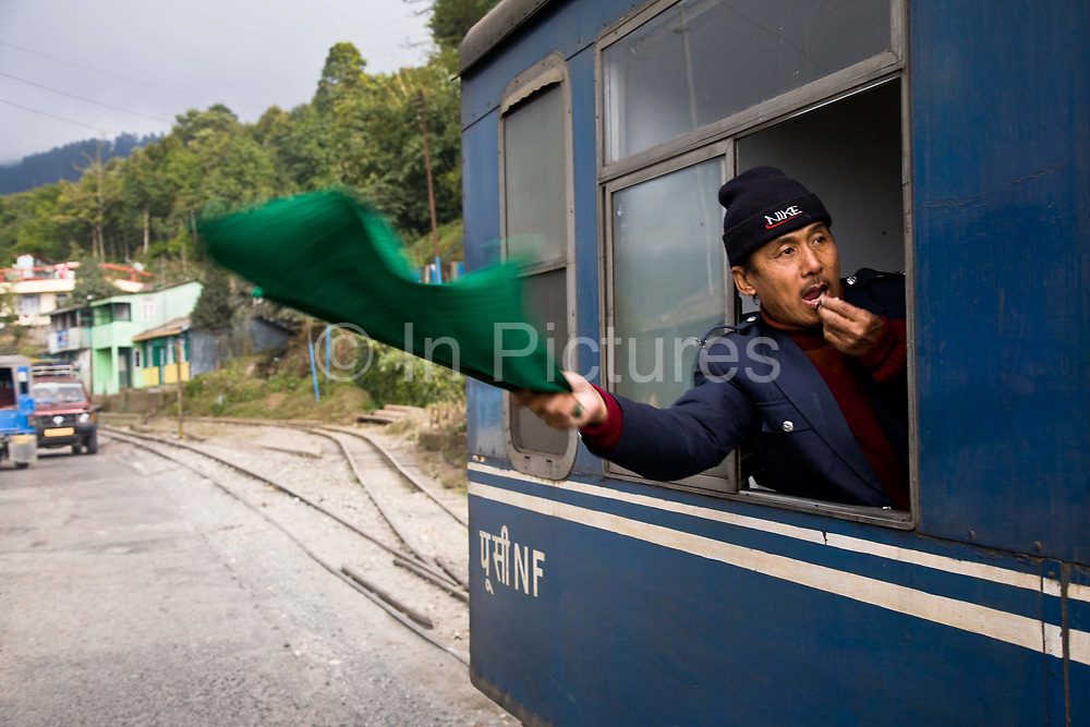 """The train conductor waving on the DHR steam train, as it leaves a station. The Darjeeling Himalayan Railway, nicknamed the """"Toy Train"""", is a narrow-gauge railway from Siliguri to Darjeeling in West Bengal, run by the Indian Railways. It was built between 1879 and 1881 and is about 86 km long. The elevation level is from about 100 m at Siliguri to about 2200 m at Darjeeling. It is still powered by a steam engine and travels daily between the two towns, as well as a shorter 32 Km route to Kurseong.  It is now classed as a World Heritage Site by UNESCO. India."""