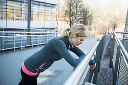 Exhausted woman resting on bridge after workout