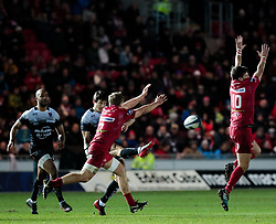 Toulon's Francois Trinh-Duc kicks through under pressure from Scarlets' Hadleigh Parkes<br /> <br /> Photographer Simon King/Replay Images<br /> <br /> European Rugby Champions Cup Round 6 - Scarlets v Toulon - Saturday 20th January 2018 - Parc Y Scarlets - Llanelli<br /> <br /> World Copyright © Replay Images . All rights reserved. info@replayimages.co.uk - http://replayimages.co.uk
