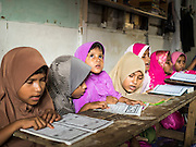 01 JUNE 2015 - KULAI, JOHORE, MALAYSIA:  Rohingya children in a madrasa (Muslim religious school) recite the Koran in Kulai, Malaysia. The Rohingya children are not allowed to attend Malaysian schools. Their madrasa is in a dilapidated building with holes in the roof and exposed wiring. The UN says the Rohingya, a Muslim minority in western Myanmar, are the most persecuted ethnic minority in the world. The government of Myanmar insists the Rohingya are illegal immigrants from Bangladesh and has refused to grant them citizenship. Most of the Rohingya in Myanmar have been confined to Internal Displaced Persons camp in Rakhine state, bordering Bangladesh. Thousands of Rohingya have fled Myanmar and settled in Malaysia. Most fled on small fishing trawlers. There are about 1,500 Rohingya in the town of Kulai, in the Malaysian state of Johore. Only about 500 of them have been granted official refugee status by the UN High Commissioner for Refugees. The rest live under the radar, relying on gifts from their community and taking menial jobs to make ends meet. They face harassment from Malaysian police who, the Rohingya say, extort bribes from them.       PHOTO BY JACK KURTZ