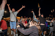 England fans throw their drinks in the air after a goal during the Euro 2020 semi final match between England and Denmark on the 7th of July 2021 at the outdoor screen at Folkestone Harbour Arm, in Folkestone, United Kingdom.