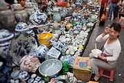 Panjiayuan weekend market. Porcelaine and ceramics shop owner having fast food lunch.