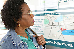 Woman looking at travel map at tram stop,