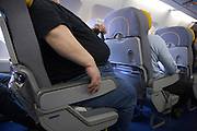 very big obese person traveling by airplane