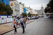 Two women with face masks walking on the lower part of Wenceslas Square in Prague. As of 21st of October 2020 people have to wear face masks outside and inside.