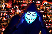 A Guy Fawkes masked man cries in front of a montage of images from the 2014 Ferguson riots.Black light